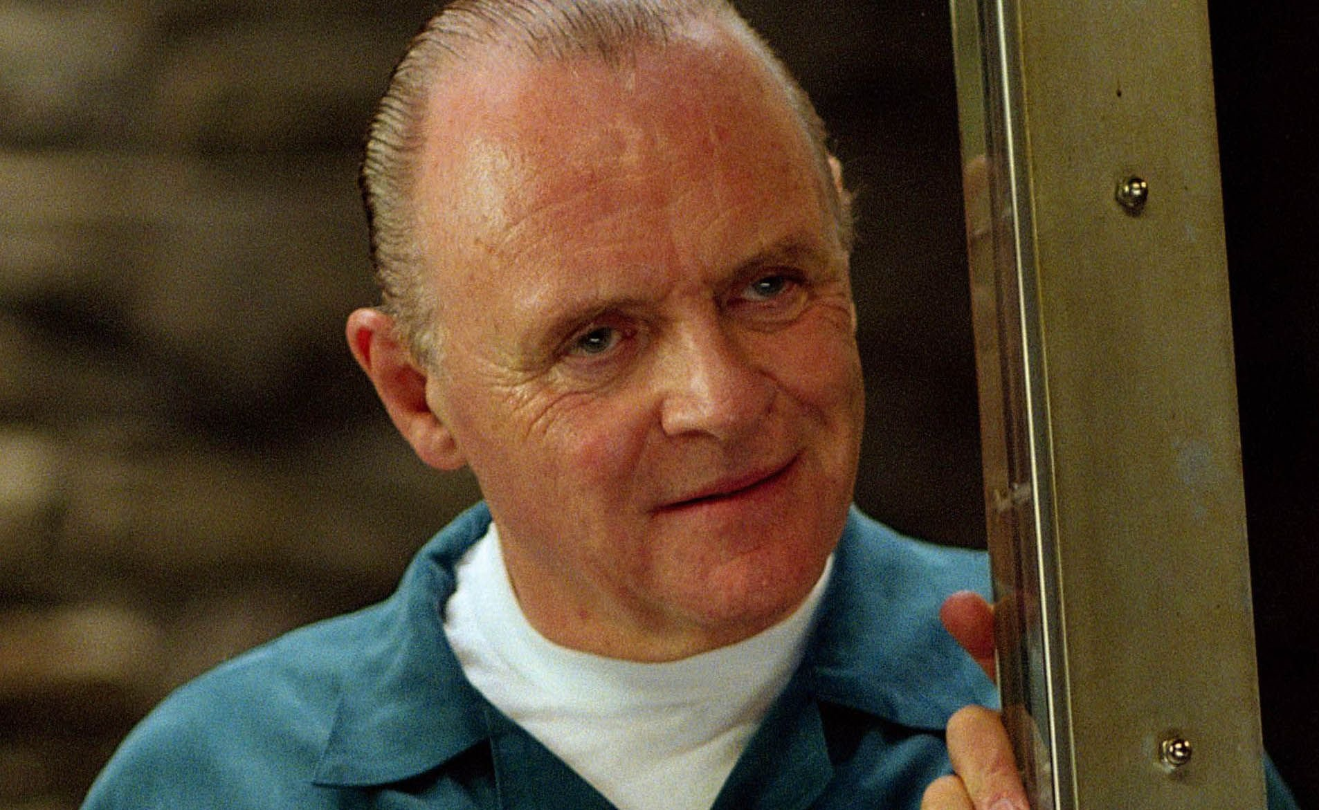 Anthony Hopkins as Hannibal Lecter in Red Dragon. Lecter, now an old man, stands up close to the camera, staring forward with a menacing smile.